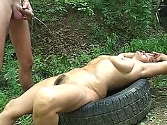 Mature slut gets pissed on in the open air